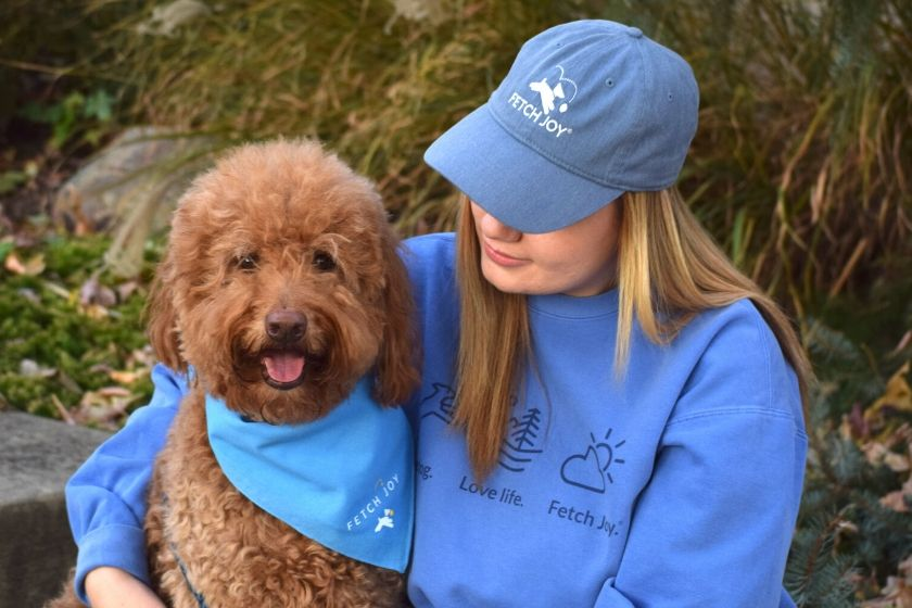 photo red goldendoodle dog wearing bandana and girl with a matching baseball cap