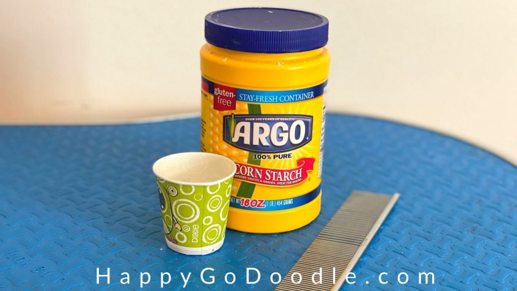 Cornstarch container, stainless steel dog comb, and dixie cup of cornstarch as examples of items needed for removing a mat from dog's hair with cornstarch, photo