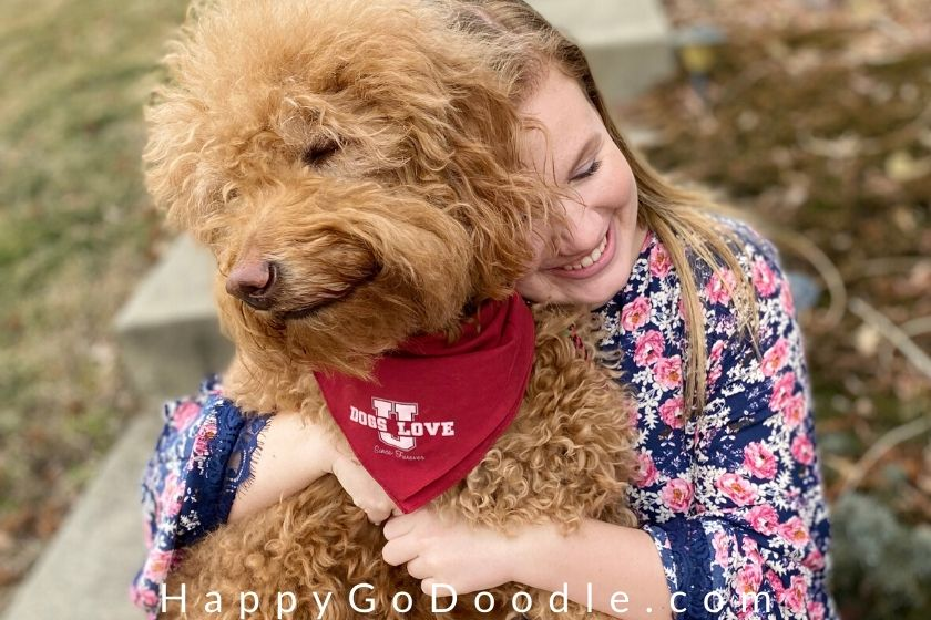 Girl hugging a Goldendoodle with a funny smile on its face, photo