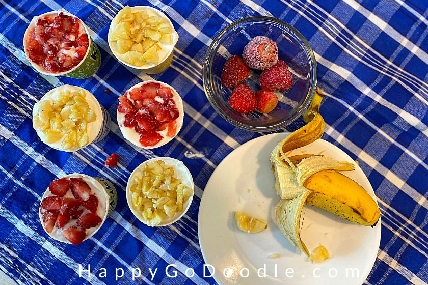 six small cups of yogurt dog treats next to a banana and bowl of strawberries, photo