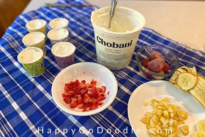 plain Greek yogurt container, bowl of diced fresh strawberries, and  Dixie cups 3/4 full of plain yogurt, photo