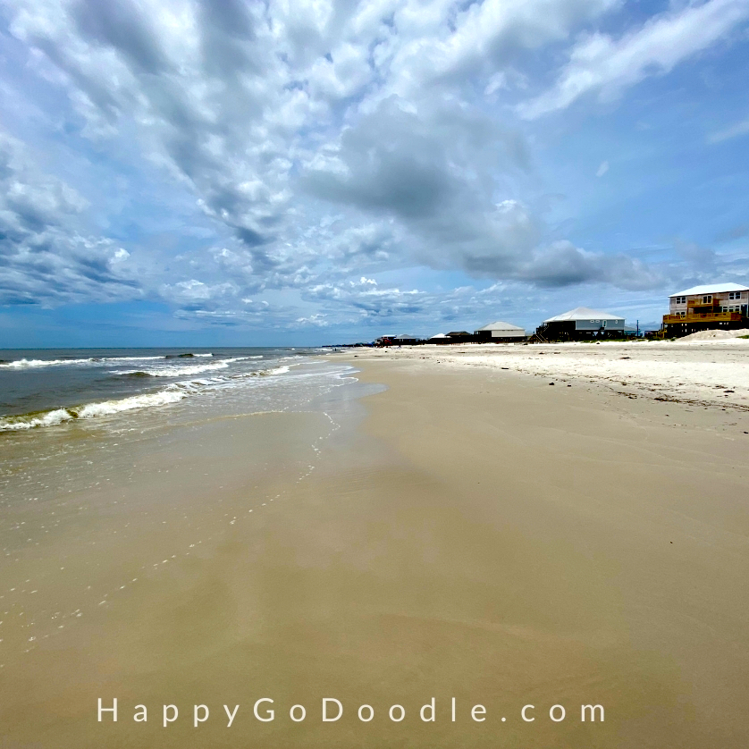 smooth, sandy, shoreline, ocean waves, and beach houses on Dauphin Island in Alabama, photo